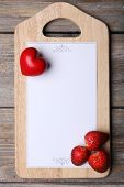 Cutting board with menu sheet of paper, heart and strawberry on rustic wooden planks background