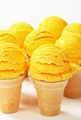 Scoops of yellow ice cream in wafer cones
