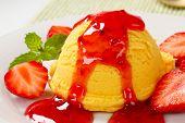 Scoop of yellow ice cream with strawberry sauce