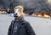 Protestor In Mask On  Ablaze Car Background