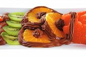 raw tropical fruits with hot chocolate cream