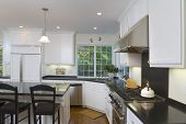 stock photo of kitchen appliance  - Interior shot of a recently remodeled kitchen featuring white custom cabinets - JPG