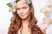 Romantic girl in floral wreath with long curly hair