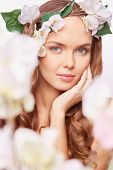 Pretty woman in floral wreath expressing calmness