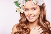 Charming girl in floral wreath looking at camera