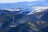 Chair lift in winter mountains background