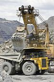 stock photo of iron ore  - Loading the iron ore into heavy dump truck at the opencast mining - JPG