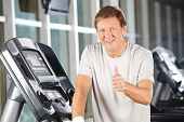 Elderly man holding thumbs up in fitness center on a treadmill