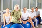 Old smiling woman in gym holding her thumbs up in fitness class