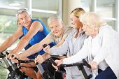 Trainer showing stopwatch to senior group on spinning bikes in gym
