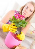 Planting colorfull flower in a flowerpot at home. Soil, girl in yellow gloves, flowerpot and flowers ready to plant on the table