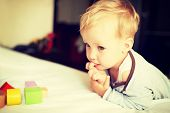 Portrait of cute little boy playing with blocks at home.