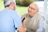 stock photo of male nurses  - Male doctor measuring blood pressure of senior man at nursing home porch - JPG
