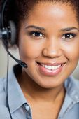 stock photo of telemarketing  - Portrait of young smiling female customer service representative wearing headset in office - JPG