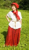 stock photo of woman red blouse  - European woman in red hat white blouse and red skirt with red scarf standing on grass meadow in park forest behind - JPG