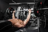 foto of bench  - Brutal athletic man pumping up muscles on bench press - JPG
