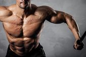 pic of arm muscle  - Brutal athletic man pumping up muscles on crossover - JPG
