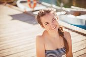 Cute girl relaxing on the dock near the boat on a Sunny day