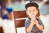 The young sailor sits in a chair and eating ice cream on the street.