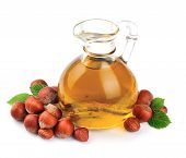 foto of filbert  - Filbert oil with hazelnuts nuts close up on white - JPG