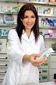 Pharmacist Giving Medicine To Customer In Pharmacy Smiling