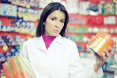 Serious Pharmacist Working On Shelf In Pharmacy