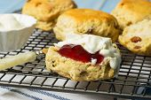 Close up of scones on cooling rack, one cut with strawberry jam and cream