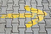 Yellow Arrow Painted On Gray Cobblestone Pavement