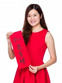 Woman holds Chinese calligraphy, phrase meaning is everything goes smooth and good luck