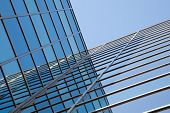 Glass Facade Of Office Building And Reflections Of Blue Sky