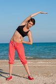 Young beautiful girl athlete playing sports on the beach