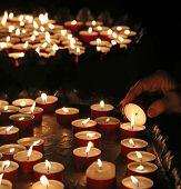 Elderly Faithful Hand Lights A Candle