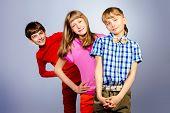 Three friends teenagers standing together. Studio shot.