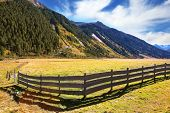 The beautiful autumn day in the Austrian Alps. Farmers alpine meadows blocked by low wooden fences
