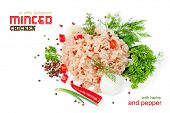 Minced chicken meat on a white background with herbs and pepper