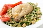Freekeh salad with chickpeas, onion, parsley, celery, and a lemon juice and olive oil dressing, and a chicken leg with tomato