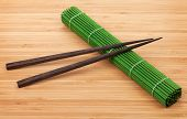 Chopsticks and bamboo mat on table