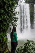 Girl Looking At Waterfall In Motion, Beautiful Misol Ha, Chiapas. Traveling Through Mexico.