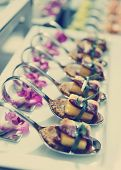 Canapes with cured ham (jamon or prosciutto) on banquet table, selective focus, toned image