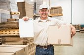Portrait of smiling delivery man with box and clipboard in warehouse