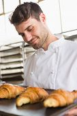 Baker showing tray of fresh croissant in the kitchen of the bakery
