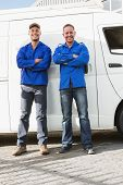 image of handyman  - Smiling handymen looking at camera in front of their van - JPG