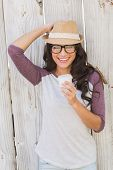 Pretty brunette holding take away coffee against bleached wooden fence