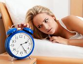 insomnia with clock at night. woman can not sleep.