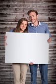 Full length portrait of couple with blank board against wooden planks