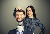 smiley woman fixing man over dark background