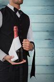Waiter holding magnum of champagne against wooden planks