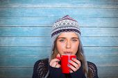Beautiful woman in warm clothing drinking coffee against wooden planks