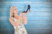 Elegant blonde admiring a shoe against wooden planks