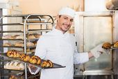Smiling baker holding trays of croissants in the kitchen of the bakery